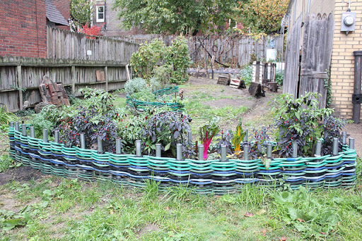 Weave Water Hoses Around Metal Poles for a Unique Way To Edge Your Garden Beds